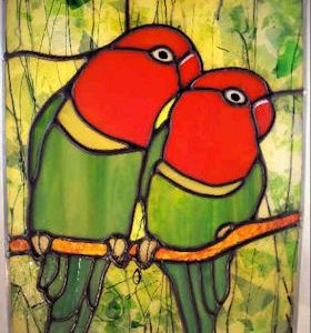 two lovebirds sitting on a branch in a leafy forest